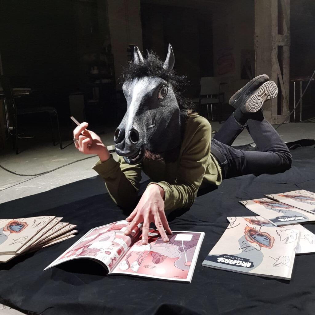 Photo von Mensch mit Pferdemaske auf dem Boden liegend und Comics schmökernd